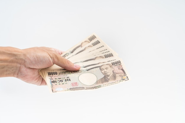 Man hand holding japanese banknote on white background