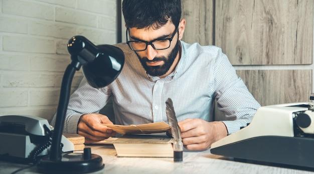 机の上の本に手紙を持っている男の手