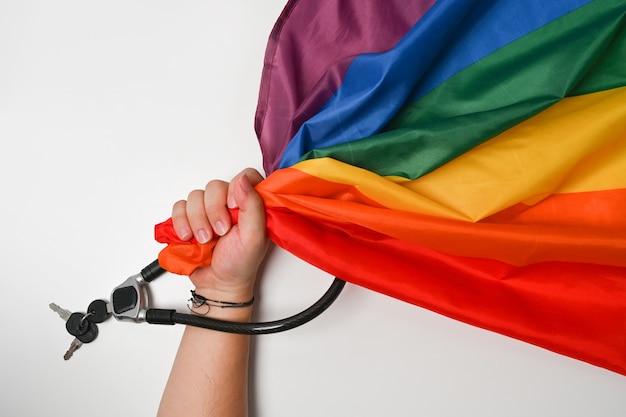 Человек рука держит флаг гордости лгбт с металлической цепью и замком. концепция любви и свободы.