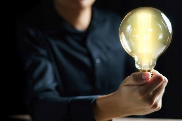 남자 손 잡고 전구입니다. 영감과 아이디어 개념입니다.