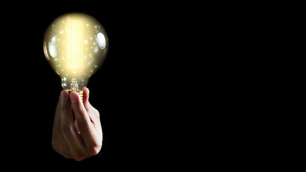 黒い背景に電球を持っている男の手。インスピレーションとアイデアのコンセプト。