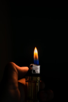 Man hand holding the lighter against black background. close-up shot.