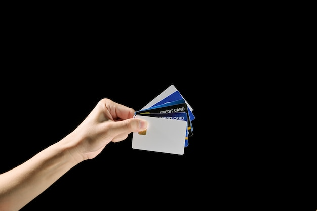 Man hand holding many credit cards on black background