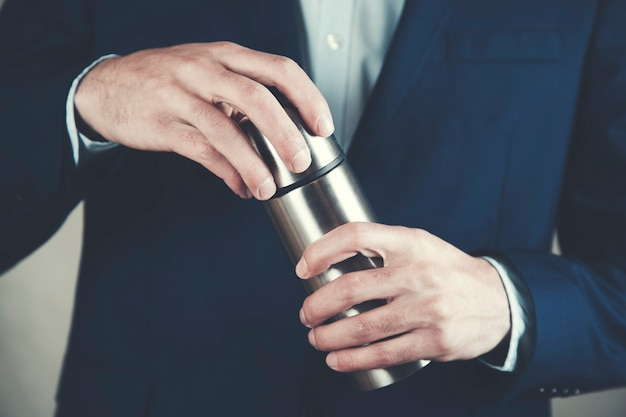 Man hand holding metal thermos