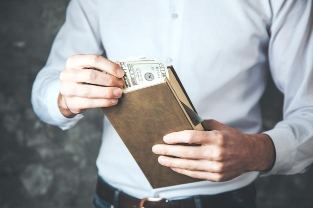 Рука человека, держащая деньги на книге
