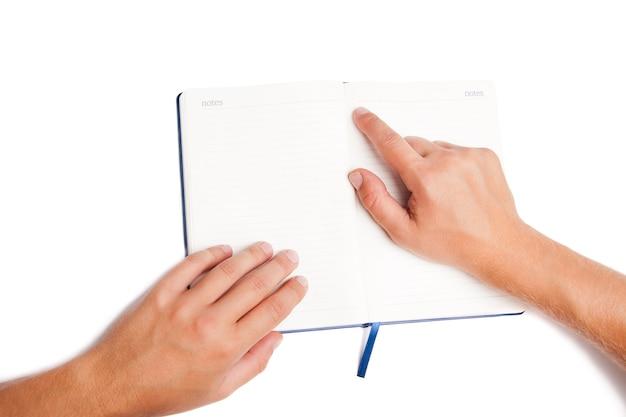 남자 손 펼친 책을 들고 흰색 배경에 고립 가리키는