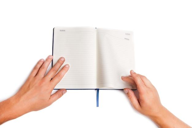 Рука человека, держащая открытую книгу, изолированные на белом фоне