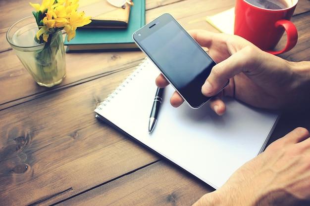 紙のノートと木製のテーブルの上のコーヒーのカップと電話を持っている男の手