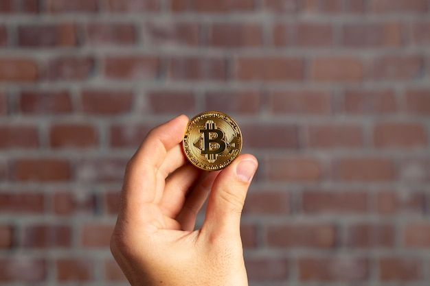 Man hand holding a physical bitcoin in front of a brick wall