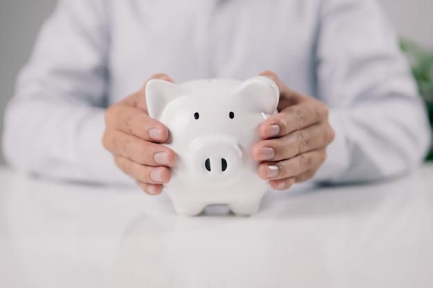 남자 손 흰색 테이블에 돼지 저금통을 들고입니다. 돈과 재정적 투자를 절약하십시오