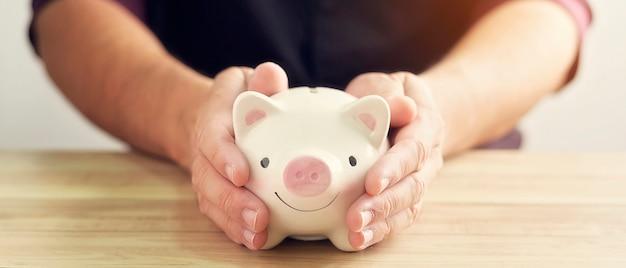 Рука человека держа копилку на деревянной таблице. деньги сбережений для будущей концепции вклада.