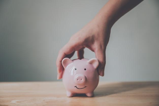 Рука человека держа копилку на деревянной таблице. экономьте деньги и финансовые вложения