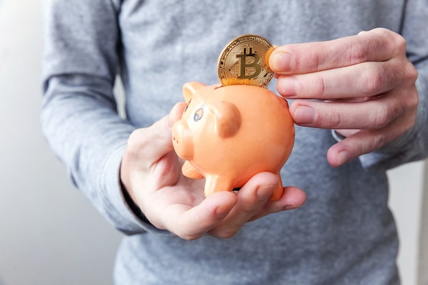 Man hand holding piggy bank with cryptocurrency golden bitcoin coin.