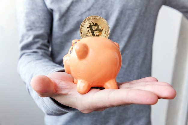 Man hand holding piggy bank with cryptocurrency golden bitcoin coin