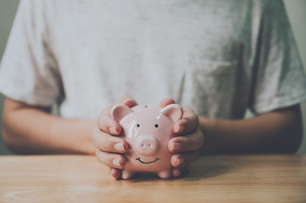 Man hand holding piggy bank on wood table