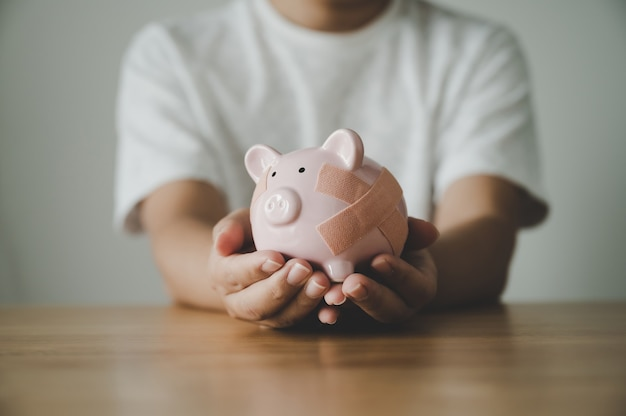 Man hand holding piggy bank on wooden table. concept of save money and finance business investment