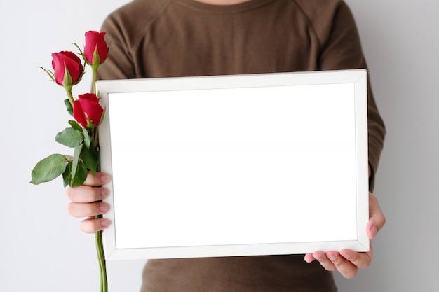 Man hand holding red roses and blank white wooden frame standing over white background