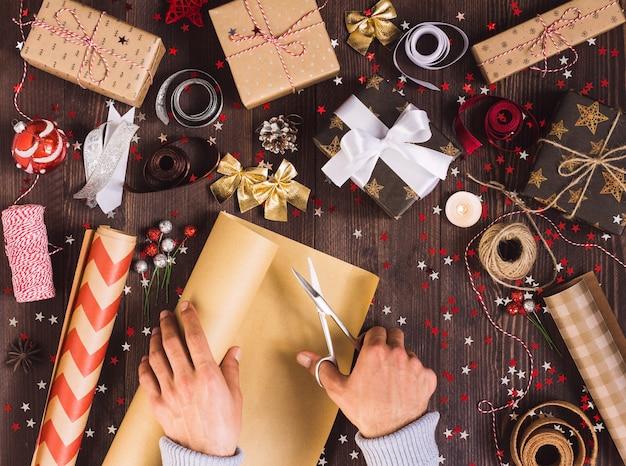 クリスマスギフトボックスをカットするためのハサミでクラフト包装紙のロールを持っている男の手