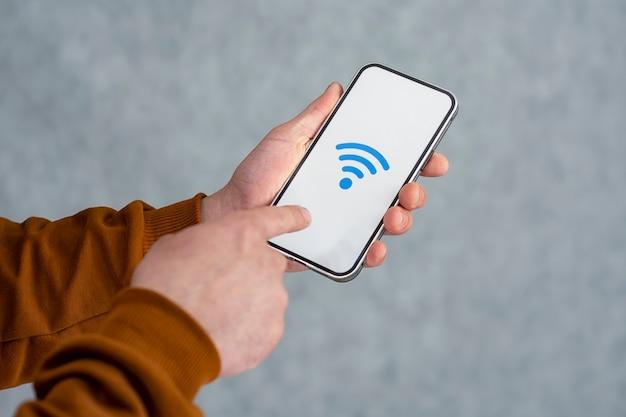 밝은 배경에 격리된 은색 스마트폰을 들고 있는 남자. 흰색 화면과 wi-fi 아이콘이 있는 전화 모형.