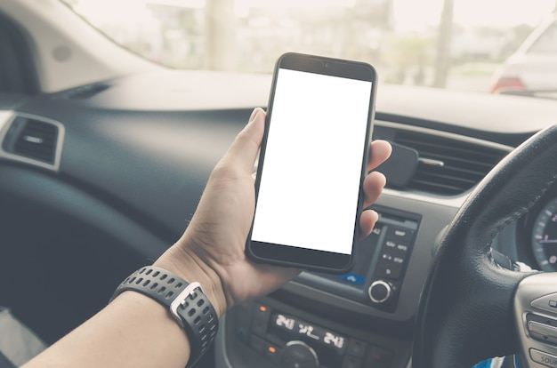 Man hand holding smartphone in car