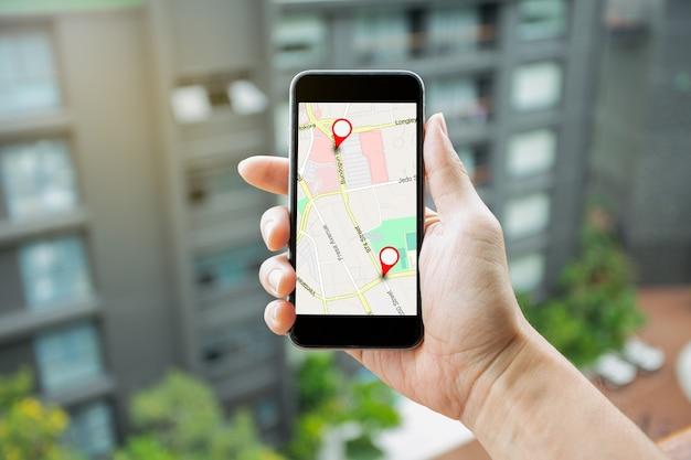 목적지 네트워크 연결을 위한 gps 지도가 있는 스마트폰을 들고 있는 남자. gps 아이콘 탐색 및 위치의 빨간색 아이콘이 있는 위치 거리 지도. 온라인 탐색 개념입니다.