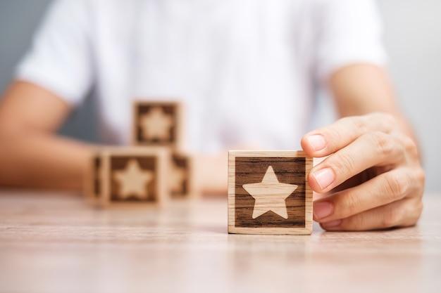 Рука человека, держащая звездный блок. клиент выбирает рейтинг для отзывов пользователей. рейтинг услуг, ранжирование, обзор клиентов, удовлетворенность, оценка и концепция обратной связи