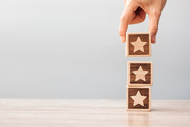 남자 손을 잡고 스타 블록입니다. 고객은 사용자 리뷰에 대한 평가를 선택합니다. 서비스 등급, 순위, 고객 리뷰, 만족도, 평가 및 피드백 개념