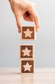 Man hand holding star block. customer choose rating for user reviews. service rating, ranking, customer review, satisfaction, evaluation and feedback concept