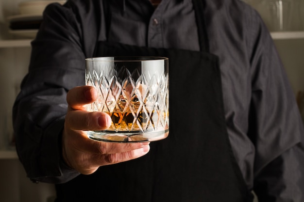 Man hand holding a textured glass of whisky