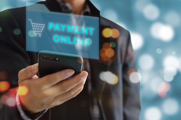 남자 손을 잡고 온라인 결제 및 온라인 쇼핑에 휴대 전화를 사용합니다. 사회적 거리두기와 재택근무 및 디지털 마케팅.