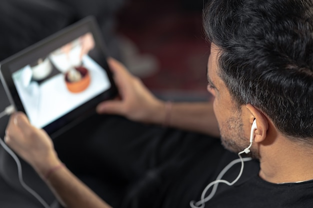 オンライン調理マスタークラスを見てデジタルタブレットを使用して男の手