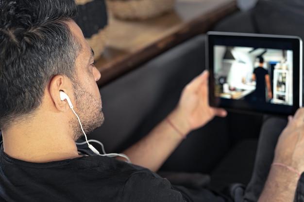 オンラインを見ているデジタルタブレットを使用して保持している男の手