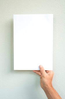Man hand holding white paper on gray background, mock up style, business concept.