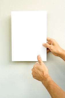 手、灰色の背景に白い紙を握って、スタイル、ビジネスコンセプトをモックアップ。