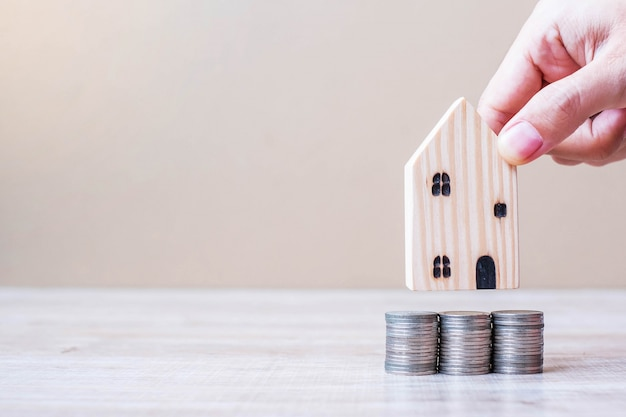 Man hand holding wooden house model over coins stack