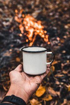 キャンプファイヤーの背景に男の手が熱いコーヒーを持っています。コンセプトアドベンチャーアクティブな休暇屋外。サマーキャンプ。