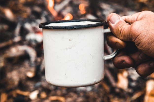 Man hand holds a hot cup of coffee at the background of the campfire. concept adventure active vacations outdoor. summer camp.