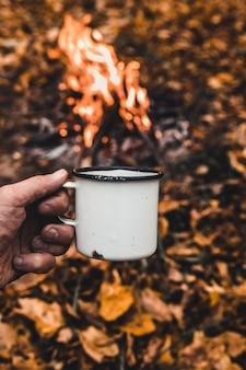 Man hand holds a hot cup of coffee at the background of the campfire.
