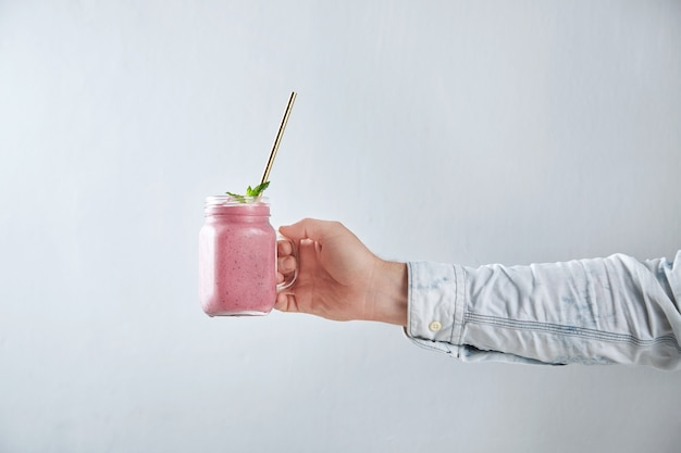 Man hand holds rustic jar with cold fresh berry smoothie with golden straw and mint leves inside. summer refreshment beverage