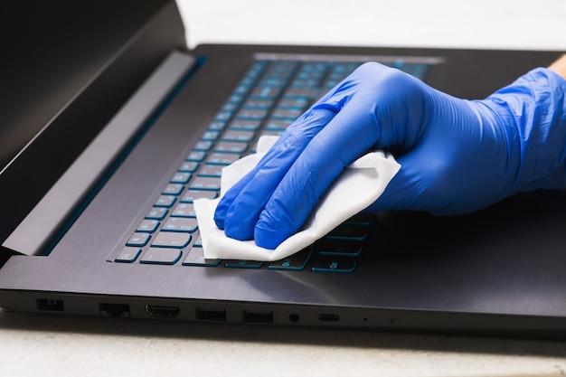 手袋をはめた男の手がノートパソコンのキーボードを抗菌剤で洗浄し、バクテリアから保護します