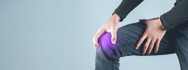 회색 배경에 통증 무릎에 남자 손