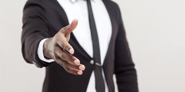 男性は黒いスーツを着て、カメラで挨拶や握手に手を差し伸べるネクタイをします。手に焦点を当てます。明るい灰色の背景のコピースペースで分離された屋内スタジオショット。