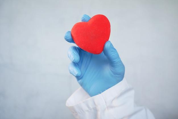 Рука человека в защитных перчатках держит красное сердце на белом фоне