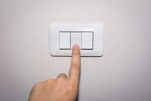 Man hand is turning on or off electrical light switch.