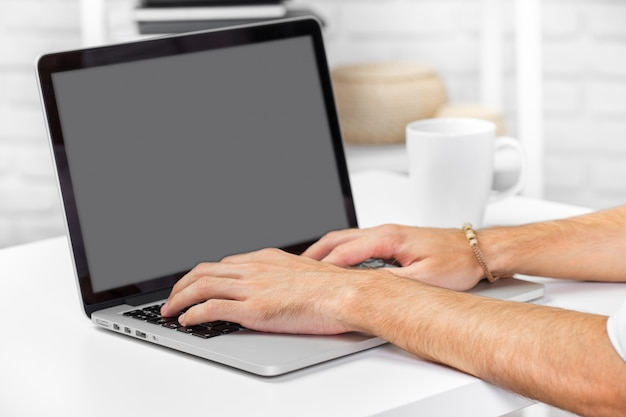 Man hand on laptop keyboard with blank screen monitor close up