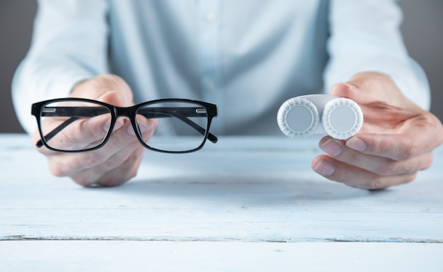 青いテーブルの上の男の手のレンズとメガネ