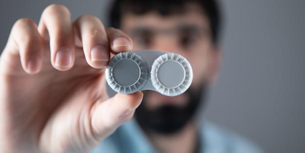 Man hand lenses box on grey