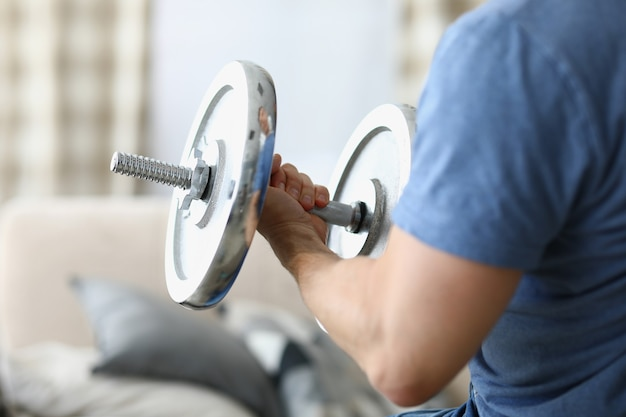Man hand lifts heavy dumbbell while swinging biceps