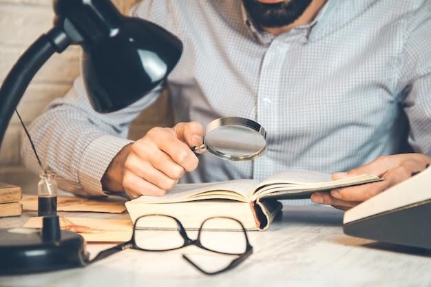 男の手の拡大鏡と机の上の本