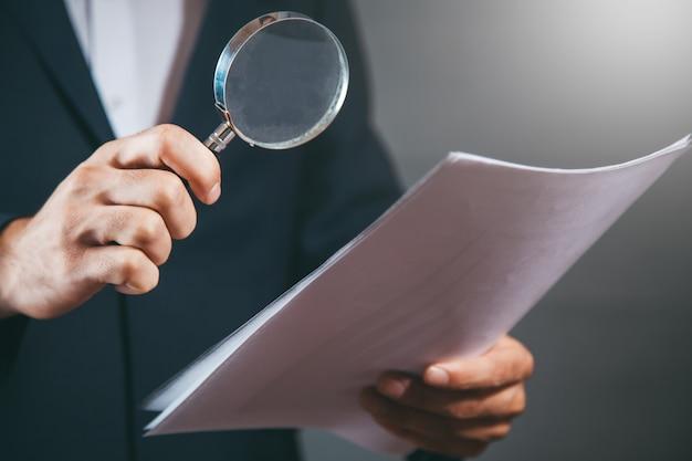 Лупа руки человека и документ на сером фоне